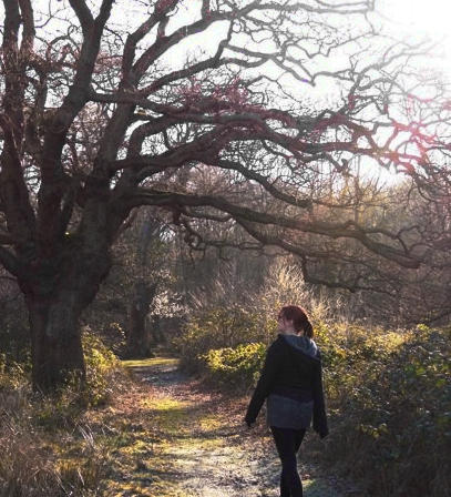 a woman in black and grey clothes walking away from the camera under an old oak tree